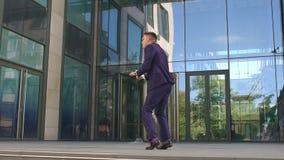 在办公楼附近的商人愉快的跳舞 影视素材