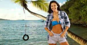 在加勒比岸和绳索轮胎附近的年轻白色女孩姿势摇摆 免版税库存照片