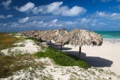 在加勒比热带绿松石沙子的遮阳伞在巴拉德罗角靠岸 免版税库存照片