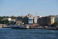 在加拉塔桥梁和金黄垫铁附近的轮渡,有圣索非亚大教堂的,在伊斯坦布尔,土耳其 库存照片