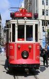在加拉塔萨雷队高中前面的一辆历史的红色电车在istiklal大道的南边 免版税库存图片