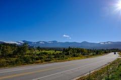 在加拿大美国边界的一条空的高速公路看见的清楚的蓝天 库存图片