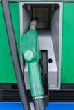 在加油站的气泵喷管前面  库存照片
