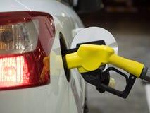 在加油站的黄色燃料喷嘴在晚上 免版税图库摄影