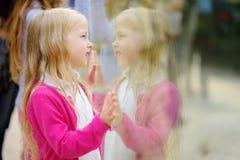 在动物园的逗人喜爱的小女孩观看的动物在温暖和晴朗的夏日 儿童观看的动物园动物通过窗口 图库摄影