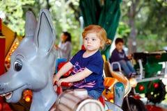 在动物的可爱的小的小孩女孩骑马在环形交通枢纽转盘在游乐场 有愉快的健康小的孩子 免版税库存图片