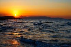 在动荡海的火红的日落 免版税库存图片