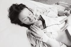 在劳方以后照顾抱着她新出生的婴孩在医院 免版税库存图片