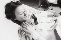 在劳方以后照顾抱着她新出生的婴孩在医院 库存图片