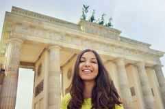 在勃兰登堡门,柏林,德国前面的愉快的微笑的女孩 美好的少妇旅行在欧洲 免版税库存图片