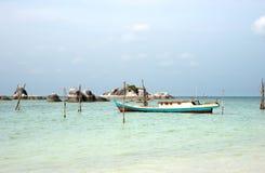 在勿里洞岛倒空渔船靠码头在绿松石色的海洋海岸在白色沙子海滩附近和与在天际的岩石 免版税库存图片