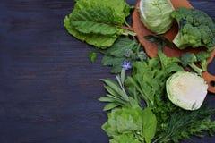 在包含叶酸,核黄素,维生素B9, B2, K, C -圆白菜, broc的绿叶蔬菜黑暗的背景的构成  库存照片