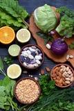 在包含叶酸,维生素B9 -绿叶蔬菜,柑橘,豆,豌豆,坚果的产品黑暗的背景的构成  免版税图库摄影