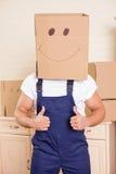 在包装期间,快乐的年轻工人取笑 免版税库存图片