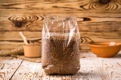 在包装的碎荞麦片在木背景 健康的饮食 免版税库存图片