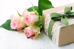 在包装纸、白色鞋带和一把绿色弓包裹的礼物盒 库存图片