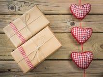 在包装纸和串包裹的小包与红色检查丝带 免版税库存照片