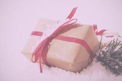 在包装纸的圣诞节礼物与减速火箭红色丝带的葡萄酒 图库摄影