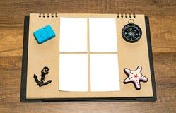 在包装纸的小空白的白色板料与蓝色照相机,船锚、指南针和星钓鱼磁铁 免版税库存照片