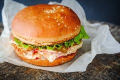 在包装纸的开胃自创汉堡在木桌上 库存图片