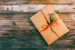 在包装纸的礼物栓与红色丝带和雏菊在与空间的木减速火箭的难看的东西背景开花文本的 免版税图库摄影