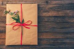 在包装纸的礼物栓与红色丝带和雏菊在与空间的木减速火箭的难看的东西背景开花文本的,顶视图关闭 库存照片