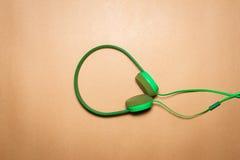 在包装纸背景的绿色耳机 库存照片