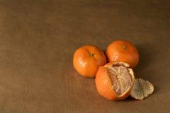在包装纸,一的三棵柑桔-半-被剥皮 库存图片