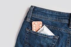 在包裹的避孕套在牛仔裤 概念安全性交 医疗保健医学、避孕和计划生育 免版税库存图片