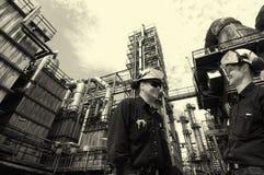 在化工精炼厂里面的油和煤气工作者 图库摄影