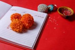 在北印度的Shubha Labh的书法文字意味善良&财富,在红色认为的笔记本,diya, 免版税库存图片