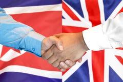 在北朝鲜和英国旗子背景的握手 免版税库存照片