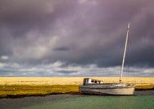 在北极岸的被放弃的渔船 库存照片