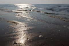 在北海的波浪的太阳强光日落的 在湿沙子和平衡天空的脚印 奥斯坦德,比利时 免版税库存图片