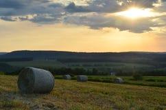 在北部纽约干草捆在农场和小山的夏天日落  图库摄影