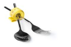 在匙子和叉子附近的测量的营养的磁带,概念和饮食 免版税库存图片