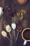 在匙子和巧克力,在真正的褐色的坚果的甜香料 库存照片