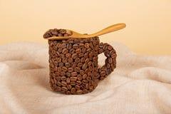 在匙子和杯子的咖啡粒 免版税库存照片