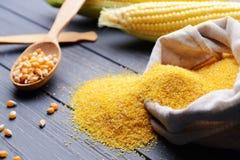 在匙子和谷物的玉米种子在灰色木桌上 免版税图库摄影