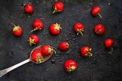 在匙子在黑暗的背景的一个湿草莓与飞溅o 库存照片