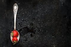 在匙子在黑暗的背景的一个湿草莓与飞溅o 库存图片