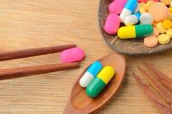 在匙子的五颜六色的医学胶囊药片有叉子和筷子的 库存图片