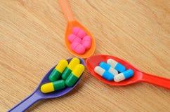 在匙子的五颜六色的医学胶囊药片 库存图片