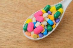 在匙子的五颜六色的医学胶囊药片 免版税库存图片