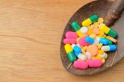 在匙子的五颜六色的医学胶囊药片 免版税库存照片