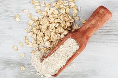 在匙子的燕麦整粒面粉用燕麦剥落 免版税库存图片