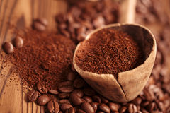 在匙子的被磨碎的咖啡在烤咖啡豆背景 图库摄影