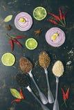 在匙子,香菜,芝麻籽,亚麻籽,在黑暗的背景的干胡椒的各种各样的香料 切片红洋葱和石灰 视图 免版税库存照片