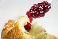 在匙子水滴的红色蔓越桔果酱在一个新鲜的新月形面包, brea 免版税库存图片