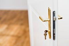 在匙孔的钥匙与美丽的金黄门把 库存照片